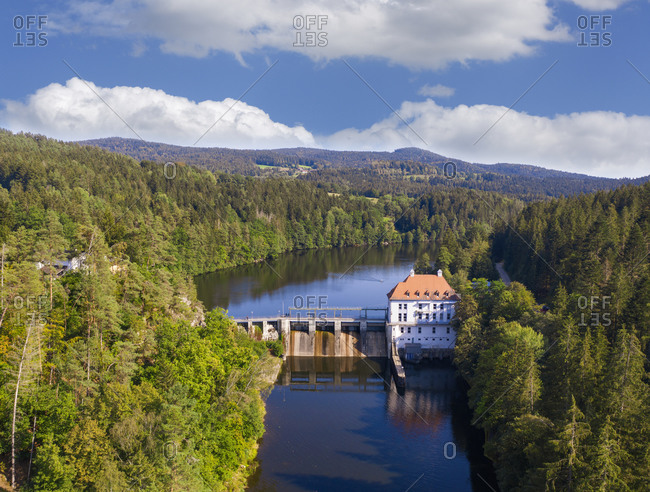Drone view of hydroelectric power station on Hollensteinsee lake and surrounding forest in summer