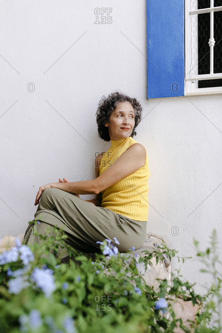 Mature woman looking over shoulder while sitting on concrete bench