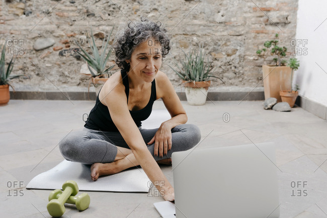 Smiling woman using laptop for learning yoga through online tutorial while sitting at back yard