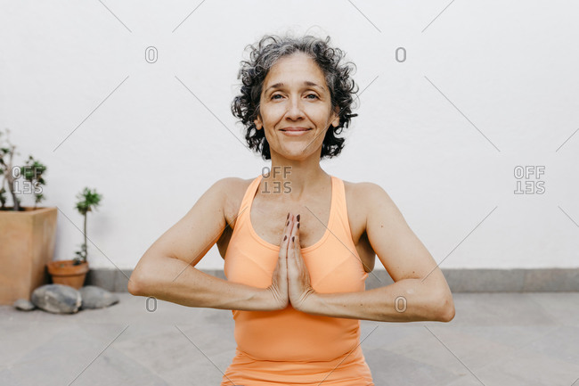 Smiling woman practicing yoga with hands clasped against white wall at back yard