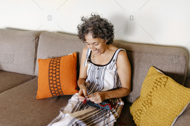 Smiling woman knitting while sitting on sofa at home