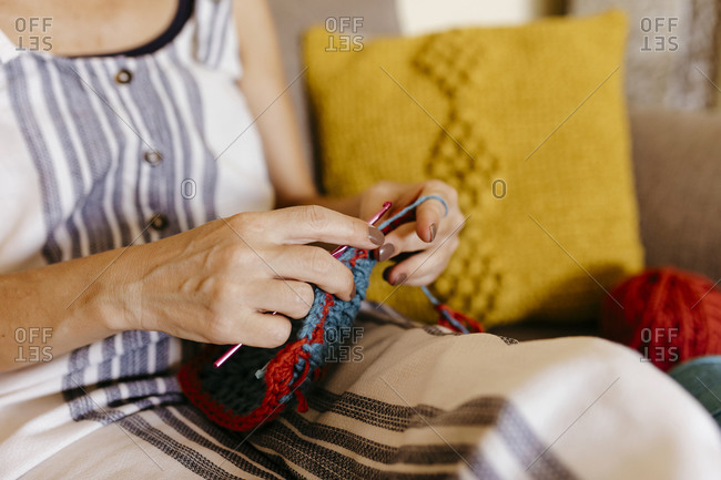 Mature woman knitting while sitting on sofa at home