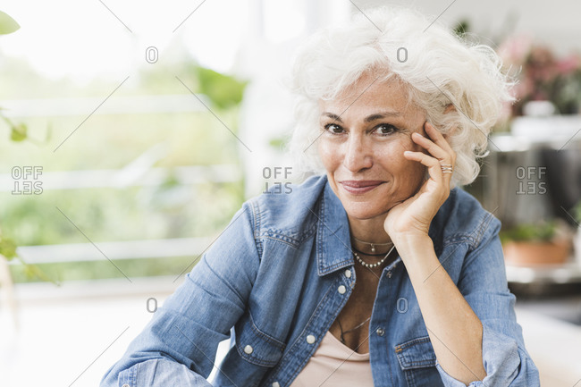 Mature woman with hand on chin sitting at home