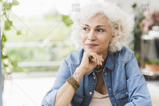 Mature woman with hand on chin looking away while sitting at home