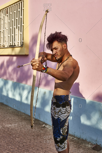 Barechested young man with bow and arrow outdoors