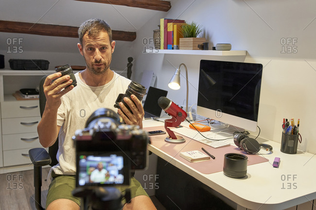 Mid adult man holding camera lenses while sitting at home