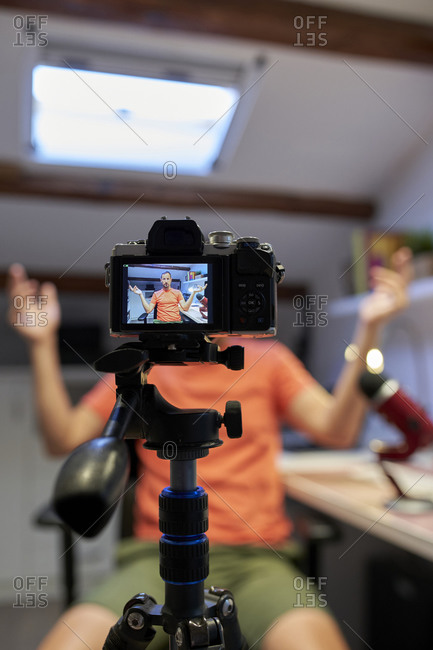 Male influencer recording video tutorial while working from home
