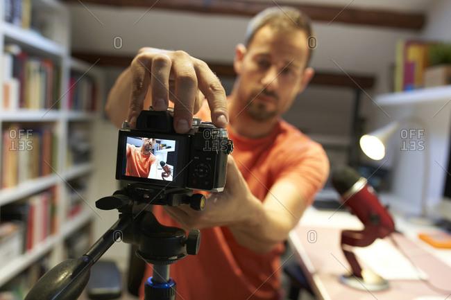 Mid adult man adjusting camera for recording video tutorial