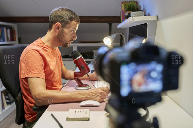 Mid adult man talking on microphone while recording tutorial video from home