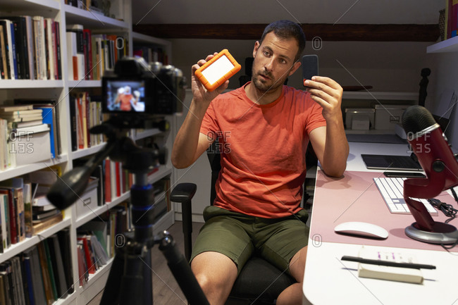 Mid adult man showing external hard disk drive while video recording on camera at home