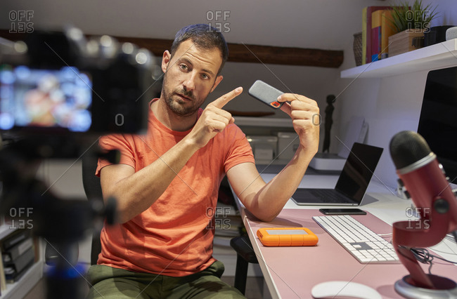 Mid adult man pointing external hard disk drive while video recording on camera at home