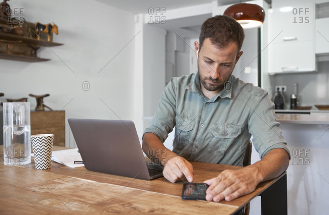 Confident mid adult businessman using smart phone while working at home