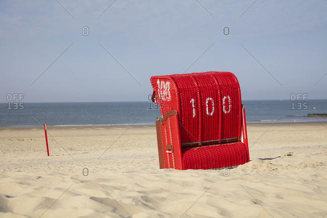 Red hooded chair on sandy beach against blue sky