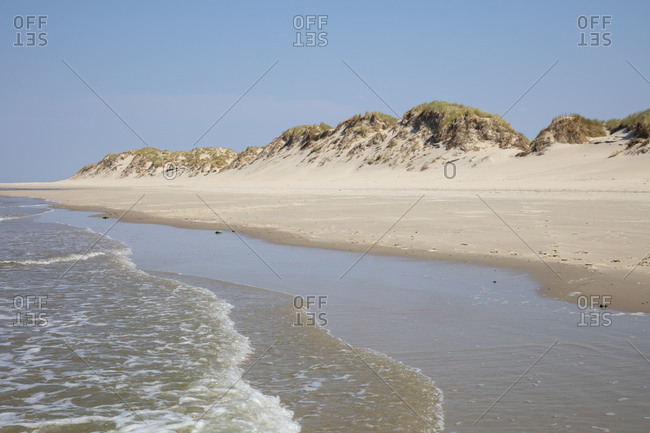 Scenic view of beach with dunes against blue sky on sunny day