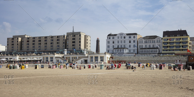 August 12, 2020: People with hooded chairs at beach against buildings in city on sunny day