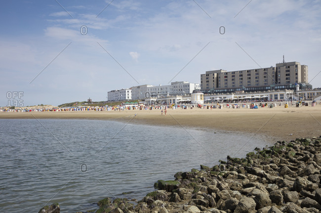 People enjoying at beach against buildings in city on sunny day