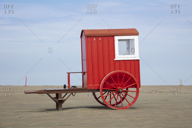 Red bathing cart on sand at beach against sky