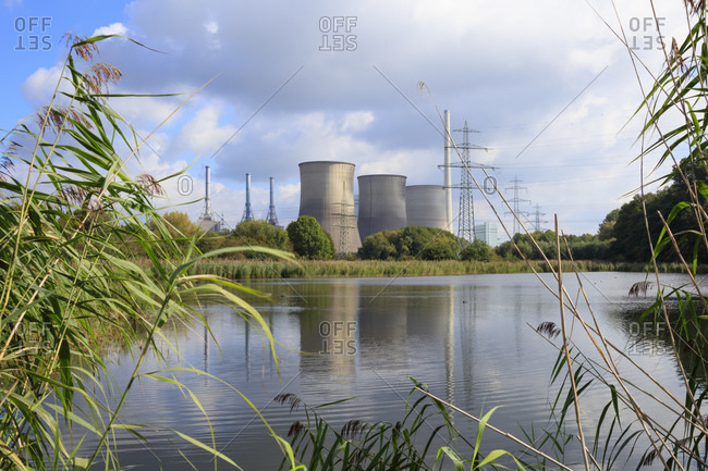 Coal-fired power station by Lippe River against cloudy sky