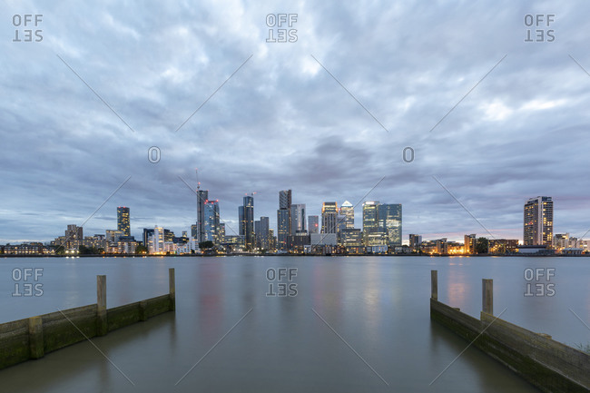 Modern skyline with skyscrapers by Thames River in city against cloudy sky at dusk- London- UK