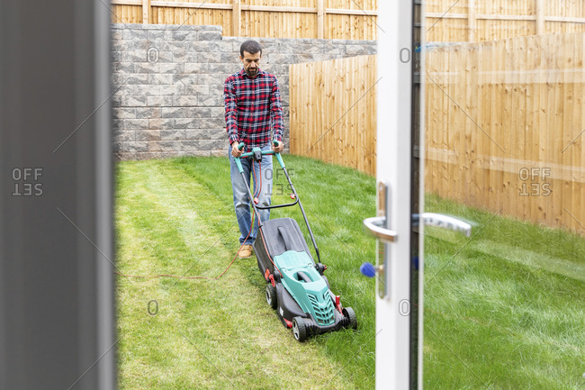 Man mowing lawn with push lawn mower at backyard