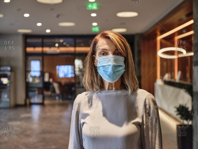 Senior woman wearing protective face mask standing in hotel lobby