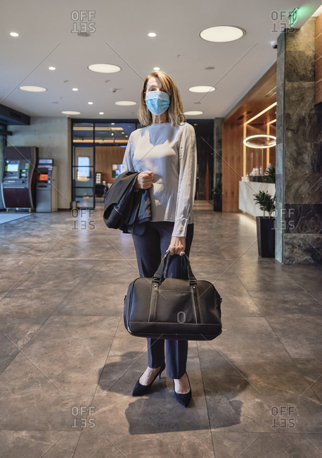 Woman wearing face mask while carrying bag standing in hotel lobby