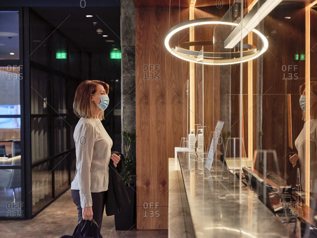 Senior woman looking at glass material while standing in hotel lobby