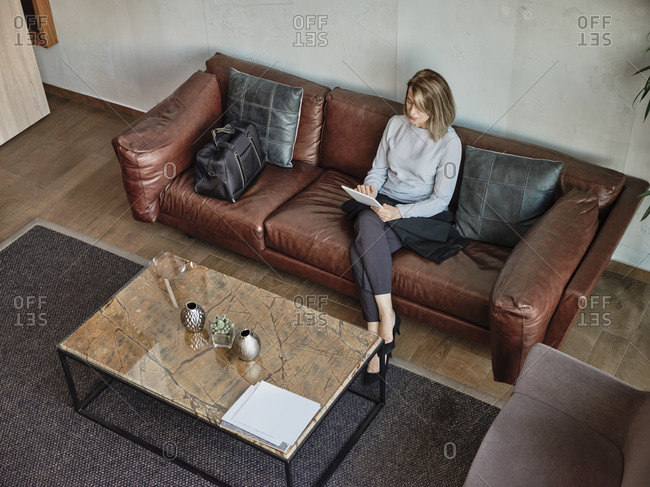 Senior woman using digital tablet while sitting in hotel lobby