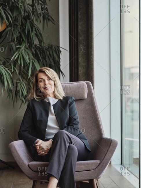 Senior woman sitting on chair in hotel lobby