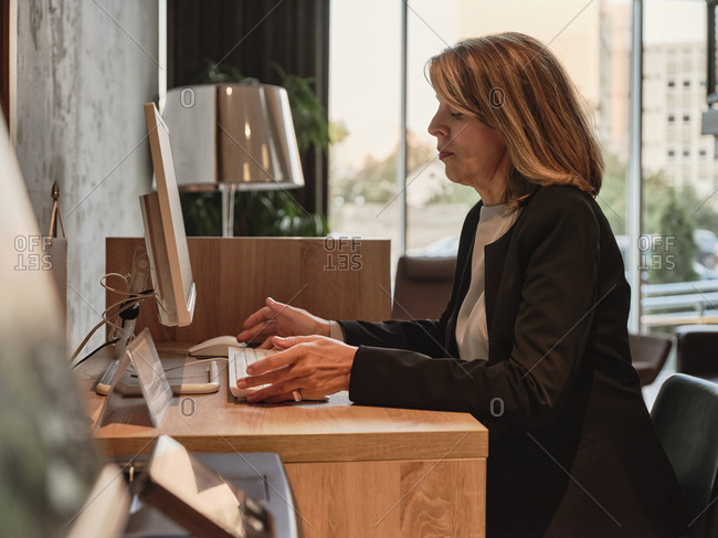 Senior woman working on computer while sitting in hotel