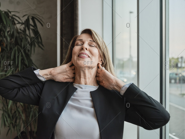 Senior woman with hands behind head standing in hotel lobby