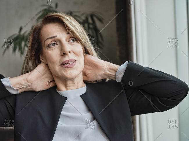 Senior woman looking away with hands behind head while standing in hotel lobby