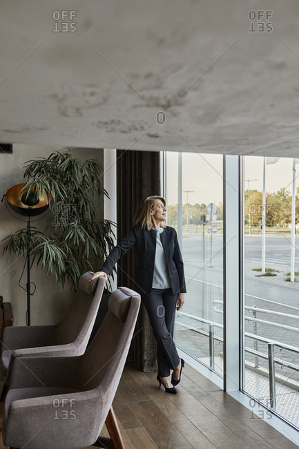 Senior woman looking away while standing in hotel lobby