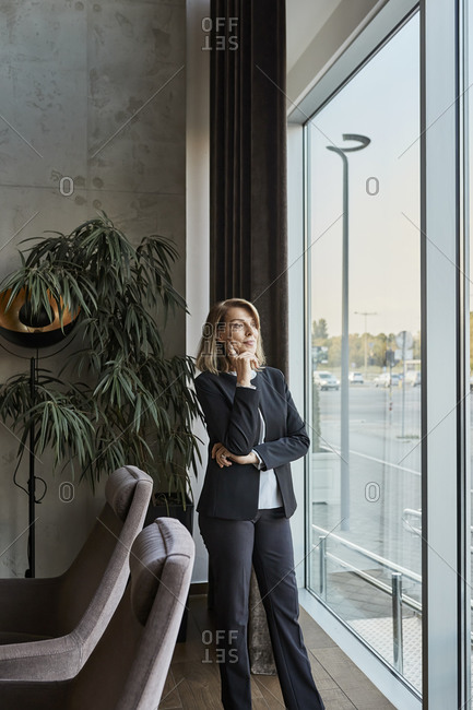 Thoughtful woman looking through window while standing in hotel lobby