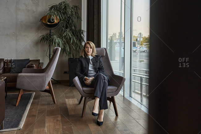 Serious senior woman sitting on chair in hotel lobby