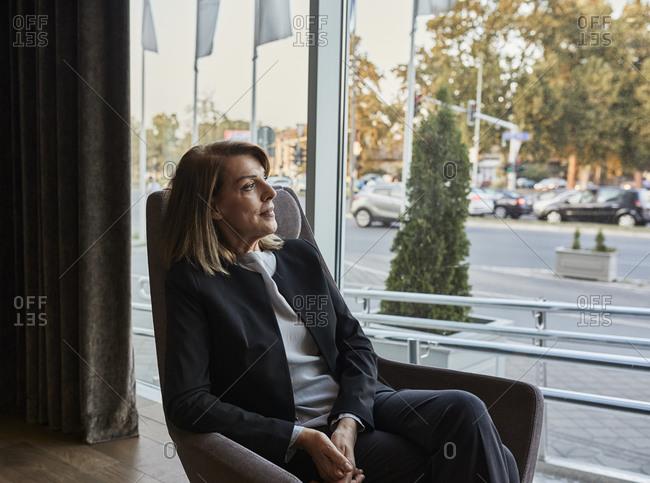 Senior woman sitting on chair looking through window in hotel lobby