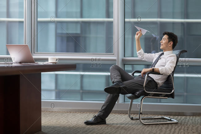 Confident Chinese businessman throwing paper plane in office
