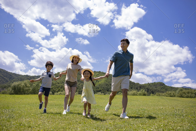 Happy young Chinese family having fun outdoors