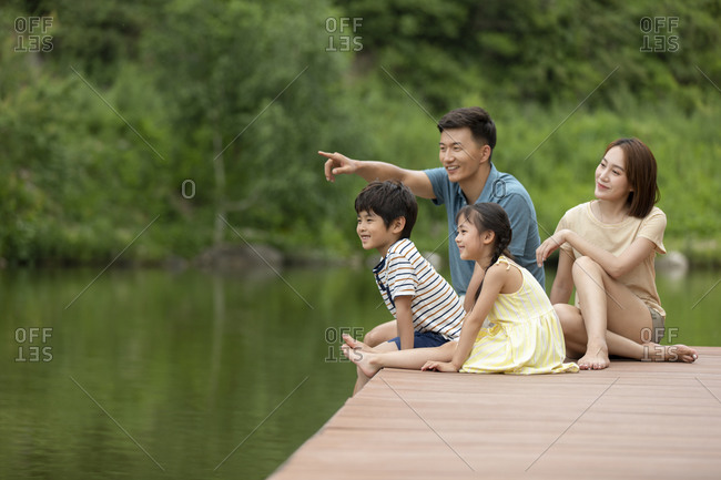 Happy young Chinese family having fun at jetty