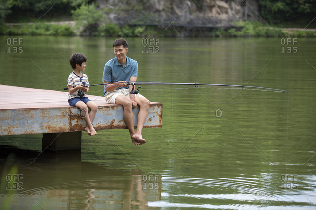 Happy Chinese father and son fishing by the river