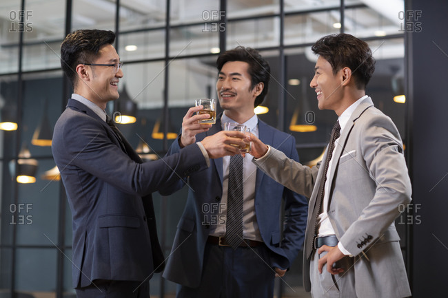 Successful Chinese businessmen drinking a toast in office