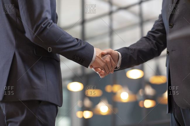 Successful Chinese businessmen shaking hands in office