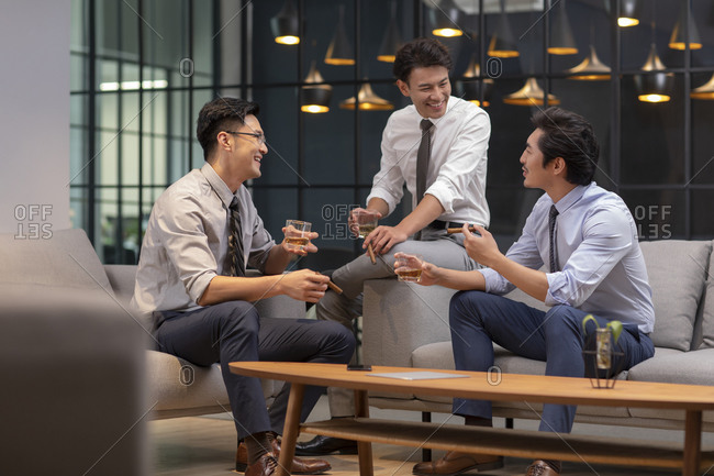 Successful Chinese businessmen drinking alcohol in office