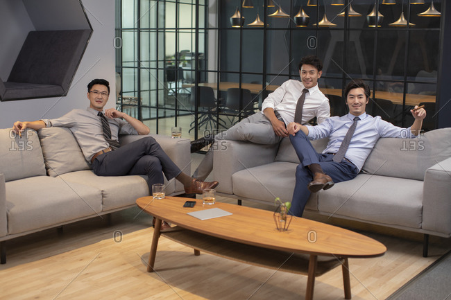 Successful Chinese businessmen sitting on sofa in office