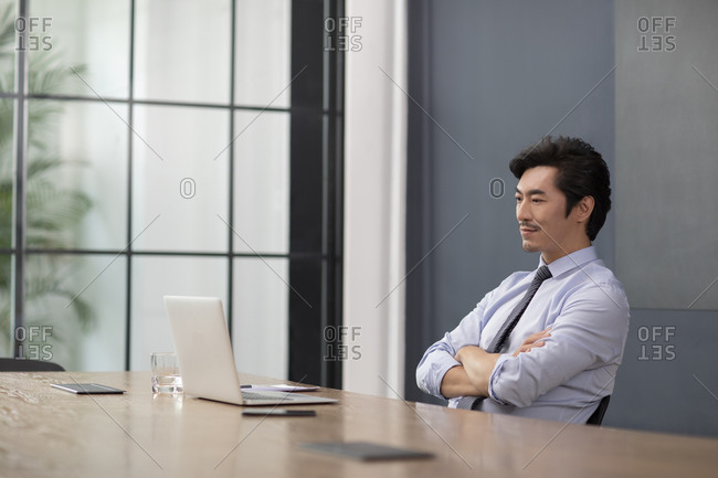Successful Chinese businessman using laptop in office