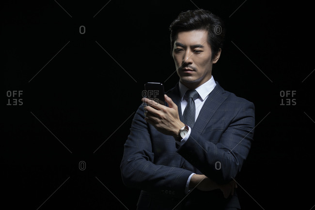 Successful Chinese businessman using smartphone