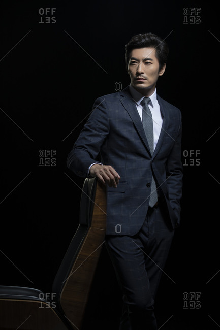 Successful Chinese businessman leaning on a chair