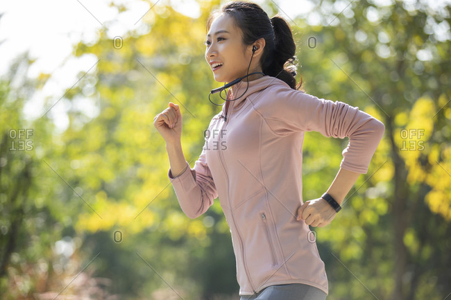 Young Chinese woman jogging in park