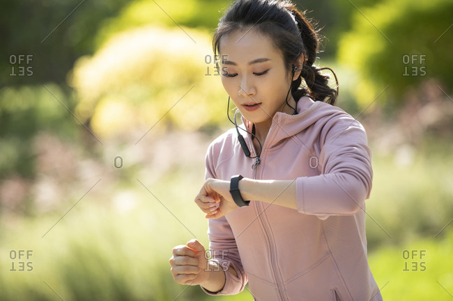 Young Chinese woman checking smart watch
