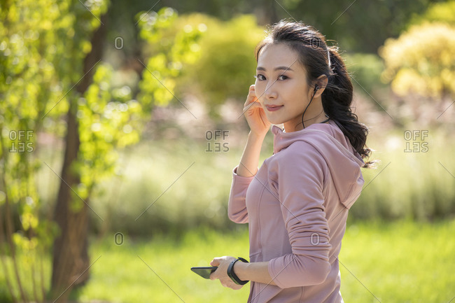 Young Chinese woman listening to music with earbuds
